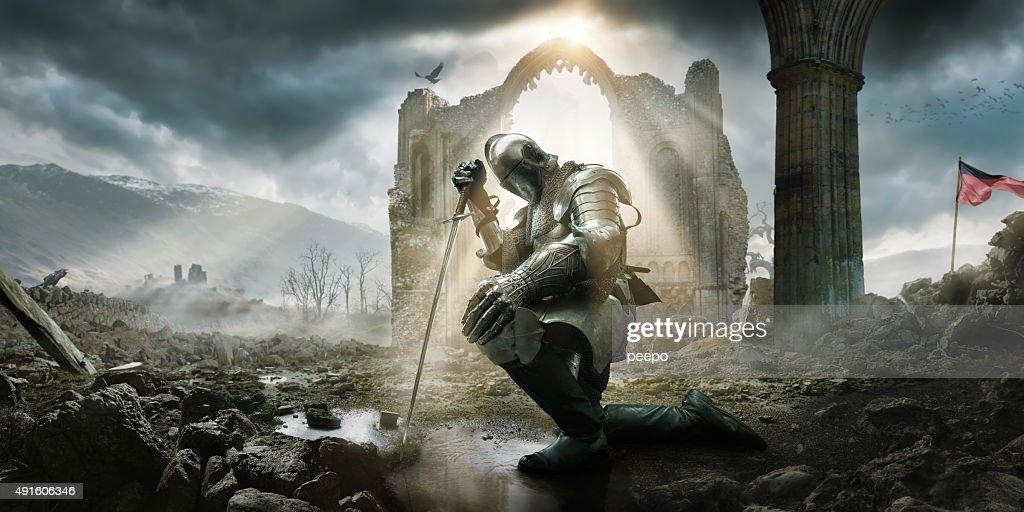 Medieval caballero arrodillarse con espada, en frente del edificio Ruina : Foto de stock