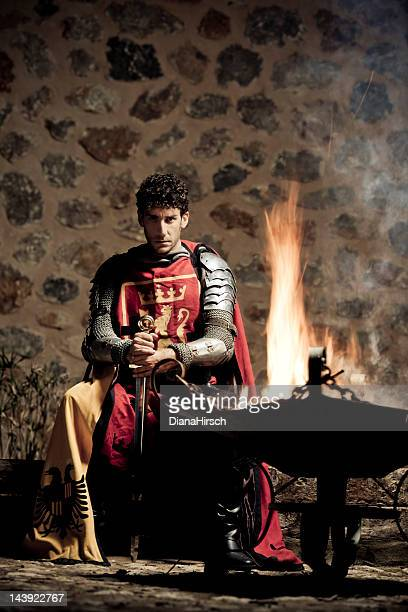 medieval knight sitting in the darkness closed to fire - koning koninklijk persoon stockfoto's en -beelden