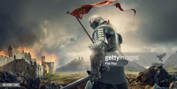 Medieval Knight With Banner And Sword Standing Near