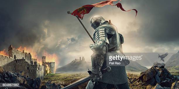 medieval knight with banner and sword standing near burning castle - castle stock-fotos und bilder