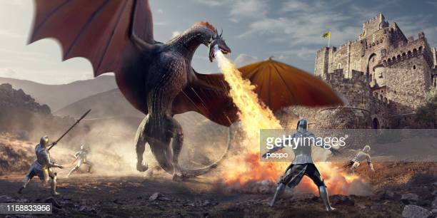 medieval knights fighting huge fire breathing dragon near castle - medieval stock pictures, royalty-free photos & images