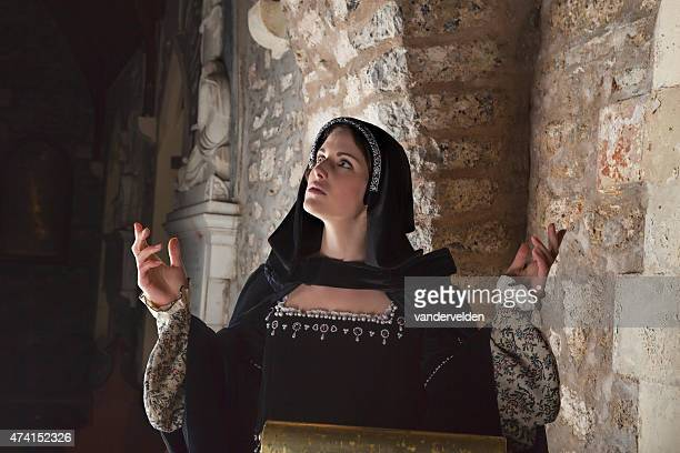 medieval lady praying from a church pulpit - religious role stock photos and pictures