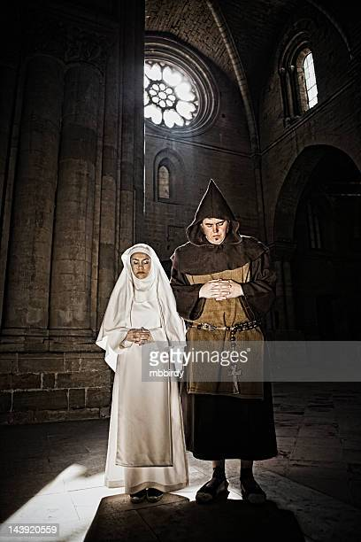 Medieval monk and nun praying in church
