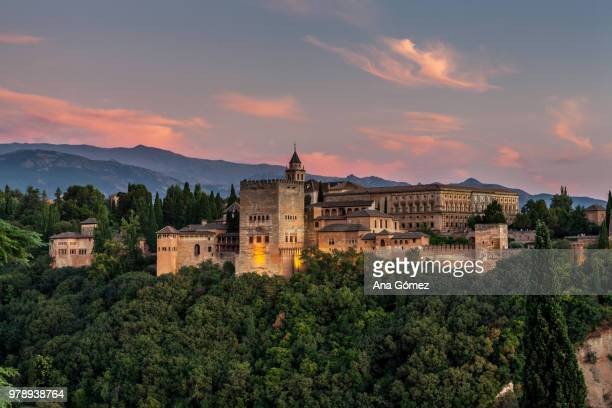 medieval palace and fortress of alhambra surrounded by forest at sunset, granada, andalusia, spain - alhambra spain stock pictures, royalty-free photos & images
