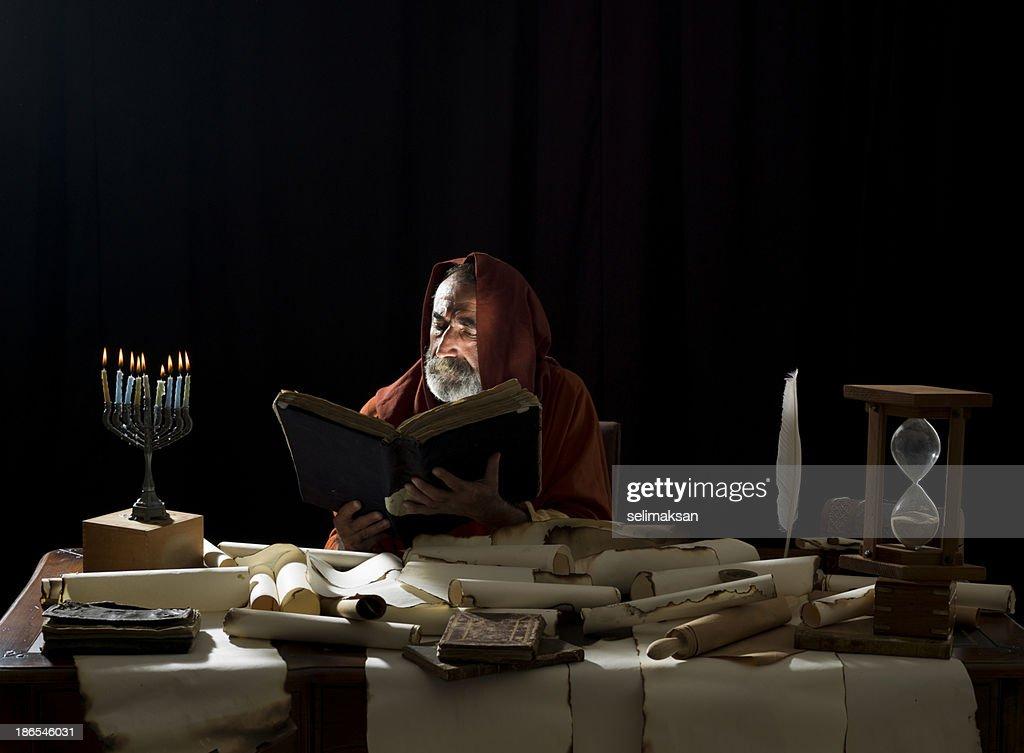 Medieval philosopher reading Torah in the light of menorah : Stock Photo