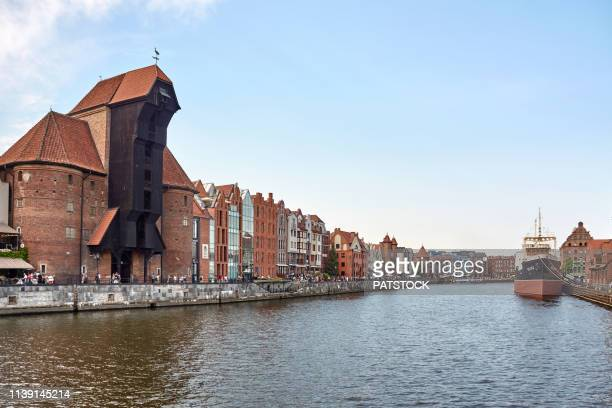 medieval port crane by the river motlawa in gdansk - motlawa river stock pictures, royalty-free photos & images