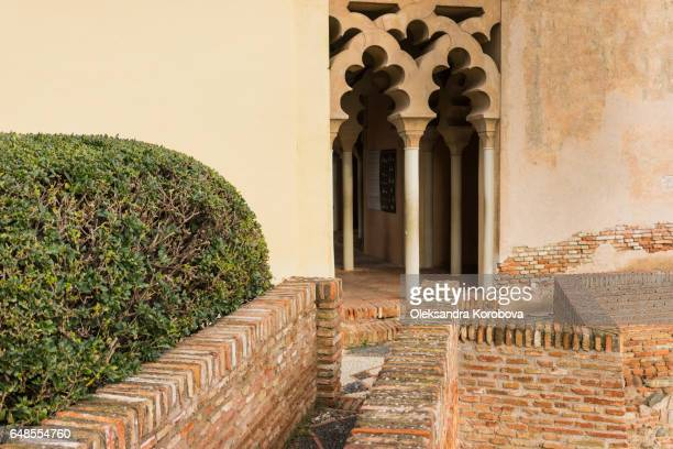 medieval stone arches and walkway by the walls and towers of an ancient alcazaba fortress - istock photos et images de collection