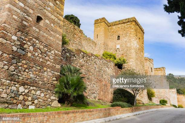 medieval stone arches, walls and towers of an ancient alcazaba fortress - istock photos et images de collection