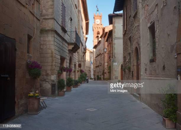 medieval street and clock tower - unesco stock-fotos und bilder