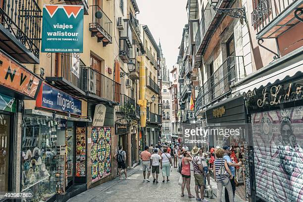 Medieval street in Toledo, Spain with people and stores