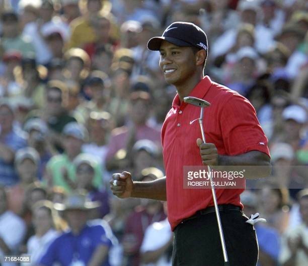 Medinah, UNITED STATES: Tiger Woods of the United States celebrates after sinking the winning putt on the 18th hole 20 August 2006 during the final...