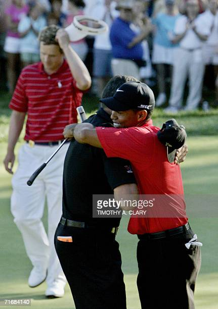 Medinah, UNITED STATES: Tiger Woods of the United States is congratulated by his caddie Steve Williams on the 18th hole after sinking the winning...