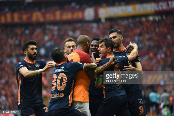 Medipol Basaksehir's defender Junior Caicara holdw back Galatasaray's Brazilian defender Marcao during an as supporters throw water onto the pitch...