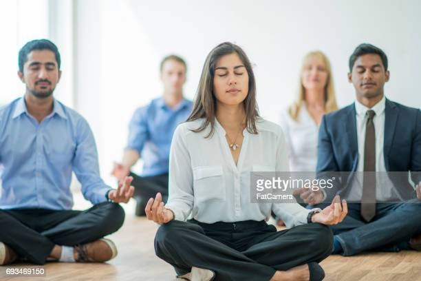 meditating at the office - wellbeing stock pictures, royalty-free photos & images