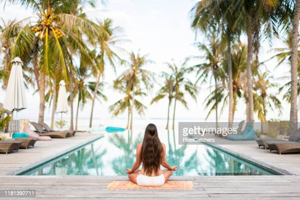 meditating in tranquillity on beautiful island resort - tourist resort stock pictures, royalty-free photos & images