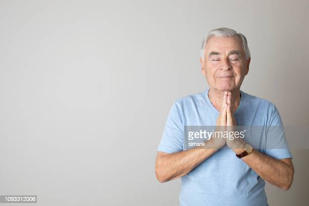 meditating senior man - breathing exercise stock pictures, royalty-free photos & images