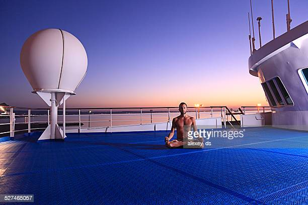 Meditation auf Schiff deck bei Sonnenaufgang