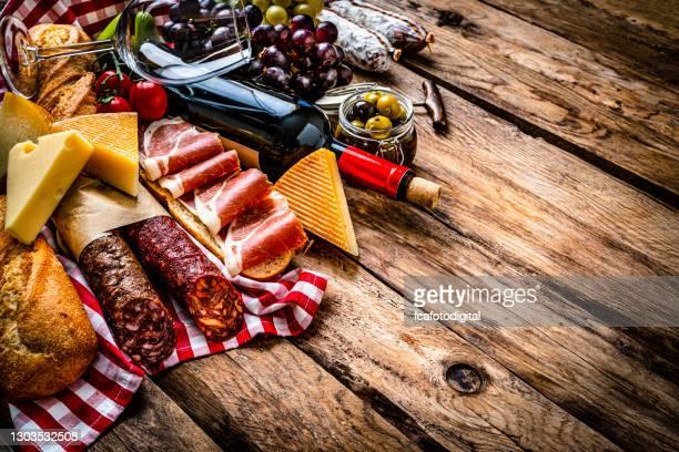 comida mediterránea: sándwich de jamón ibérico, queso y vino tinto sobre mesa de madera - cultura española fotografías e imágenes de stock