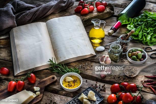 素朴なテーブルの上に地中海の食材、スパイス、スパイス - 料理本 ストックフォトと画像
