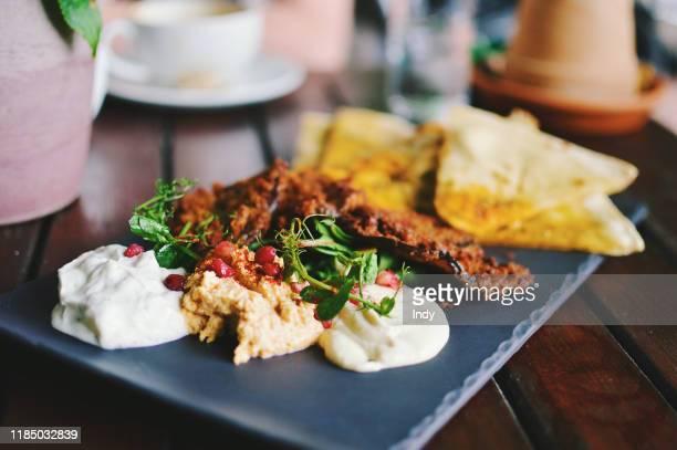 mediterranean mezze with flat bread, hummus, tzatziki, taramasalata and fried eggplant - greek food stock pictures, royalty-free photos & images