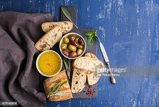 Mediterranean snacks set. Olives, oil, herbs and sliced ciabatta bread on black slate stone board over painted dark blue background
