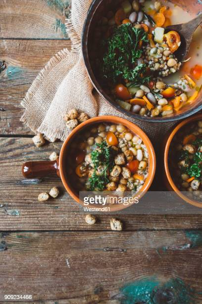 Mediterranean soup in copper pot and terracotta bowls on wood