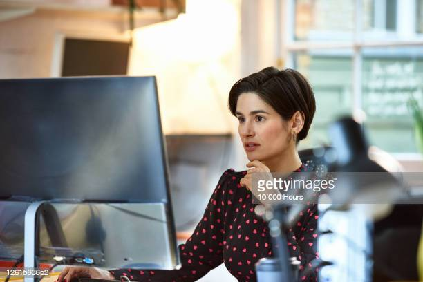 mediterranean woman using computer in office - one mid adult woman only stock pictures, royalty-free photos & images