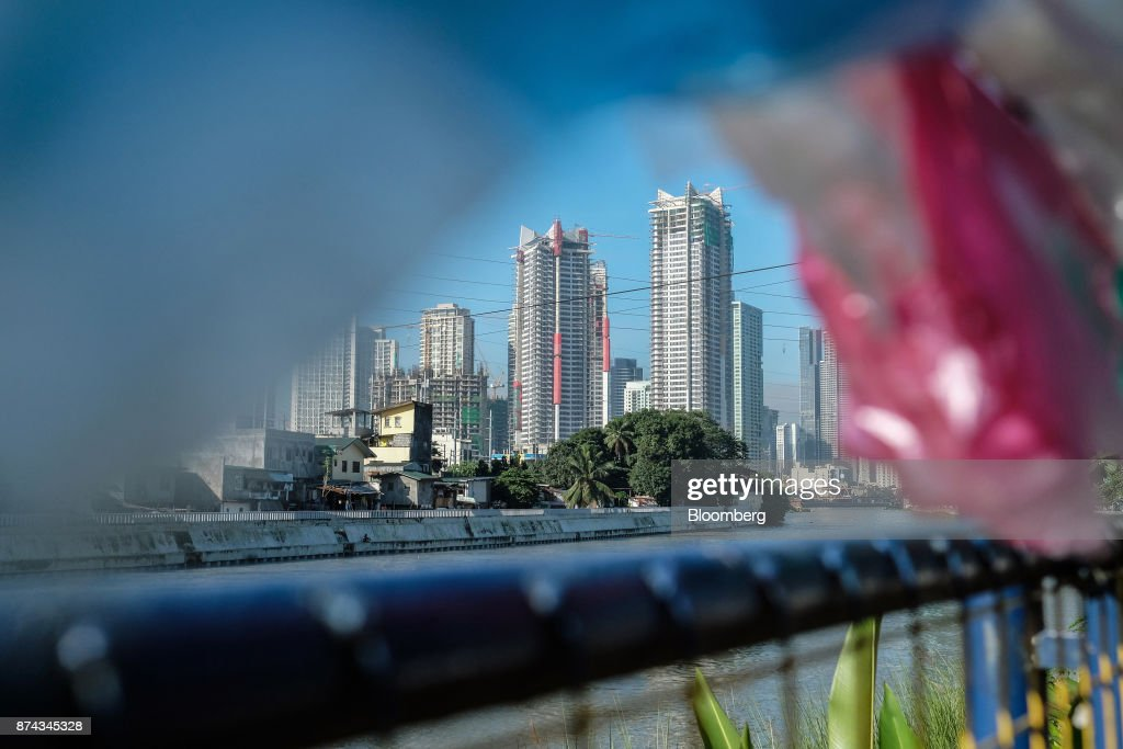 Medium and high-rise real estate stands beyond low-cost housing on the Pasig River in Mandaluyong, Metro Manila, Philippines, on Tuesday, Nov. 14, 2017. Economists are forecasting the Philippines to be among the first to raise interest rates in the region and the International Monetary Fund saidlast week the central bank should be ready to tighten if there are signs of overheating. Photographer: Veejay Villafranca/Bloomberg via Getty Images