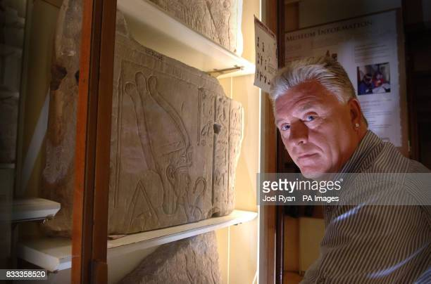 Medium and psychic Derek Acorah examines hieroglyphics on a stone tableau at the Petrie Museum of Egyptian Archaeology in central London