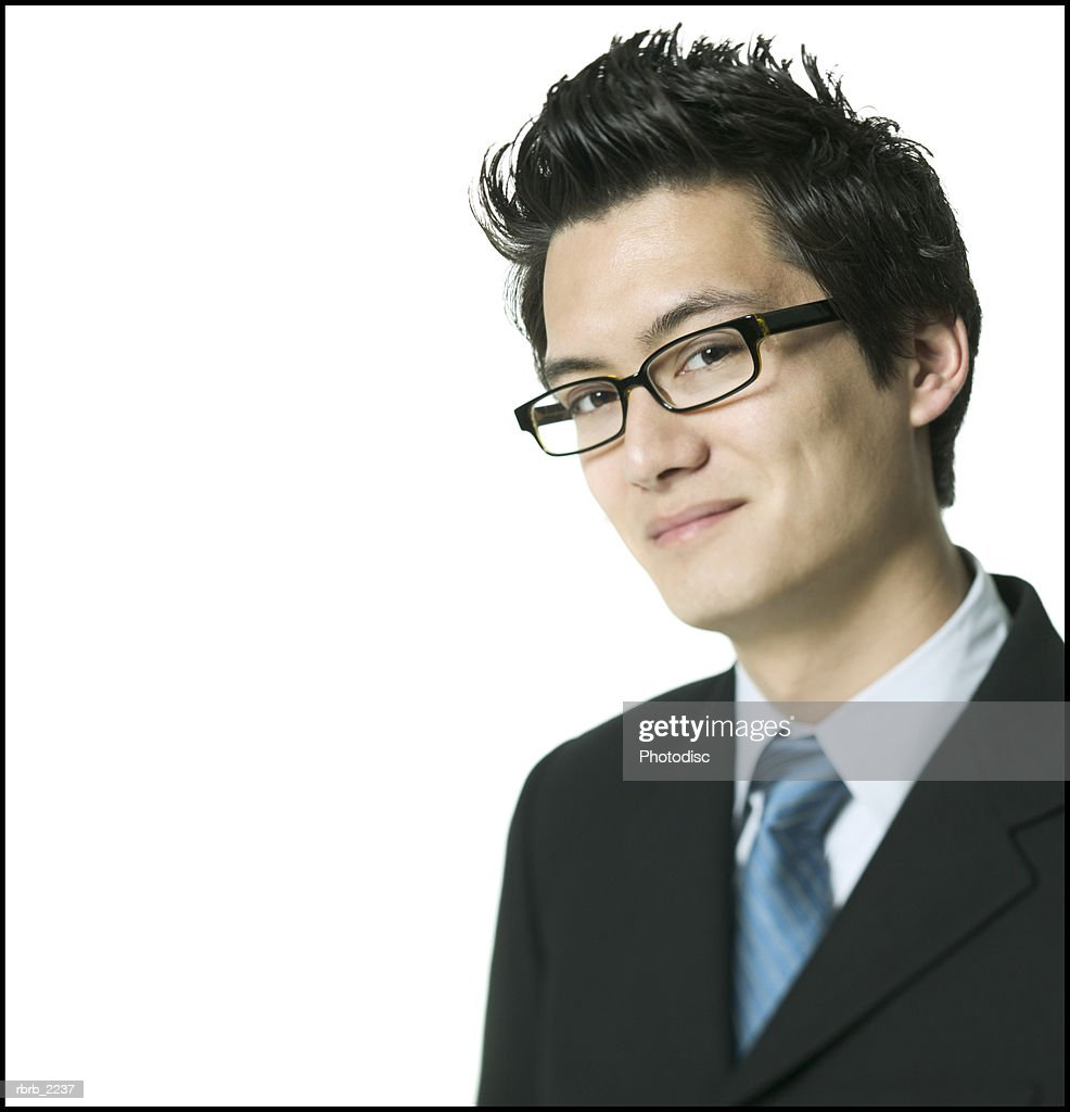 medium close up of a young adult busines man in a dark suit as he looks confidently at the camera : Foto de stock