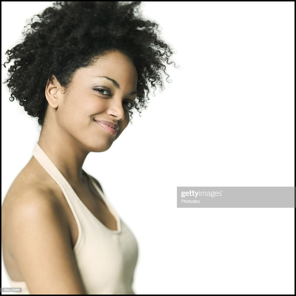 medium close up of a young adult female in a tan tank top as she turns and smiles : Foto de stock