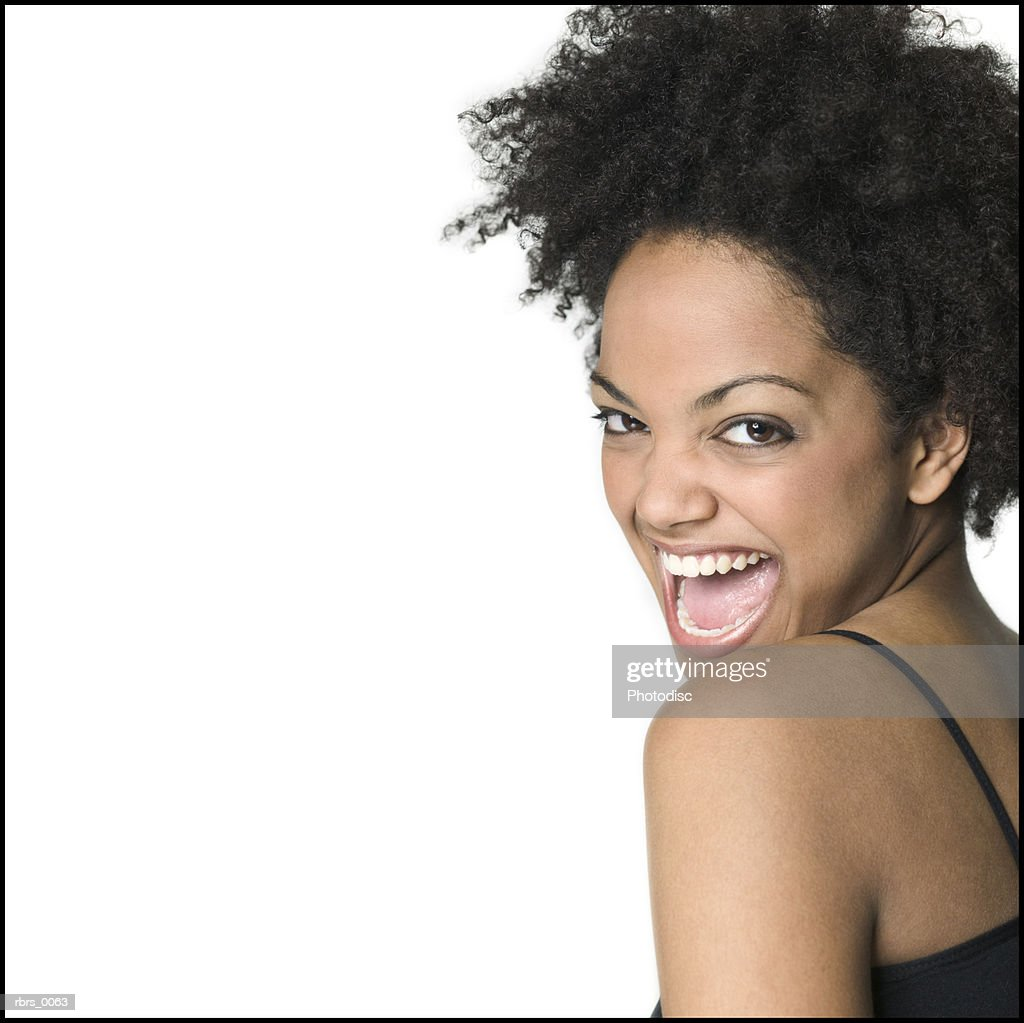 medium close up of young adult female in a black tank top as she looks over her shoulder and laughs : Foto de stock