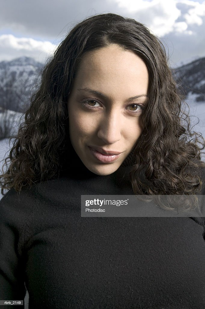 medium close up portrait of ayoung adult woman as she smiles near a winter backdrop : Stockfoto