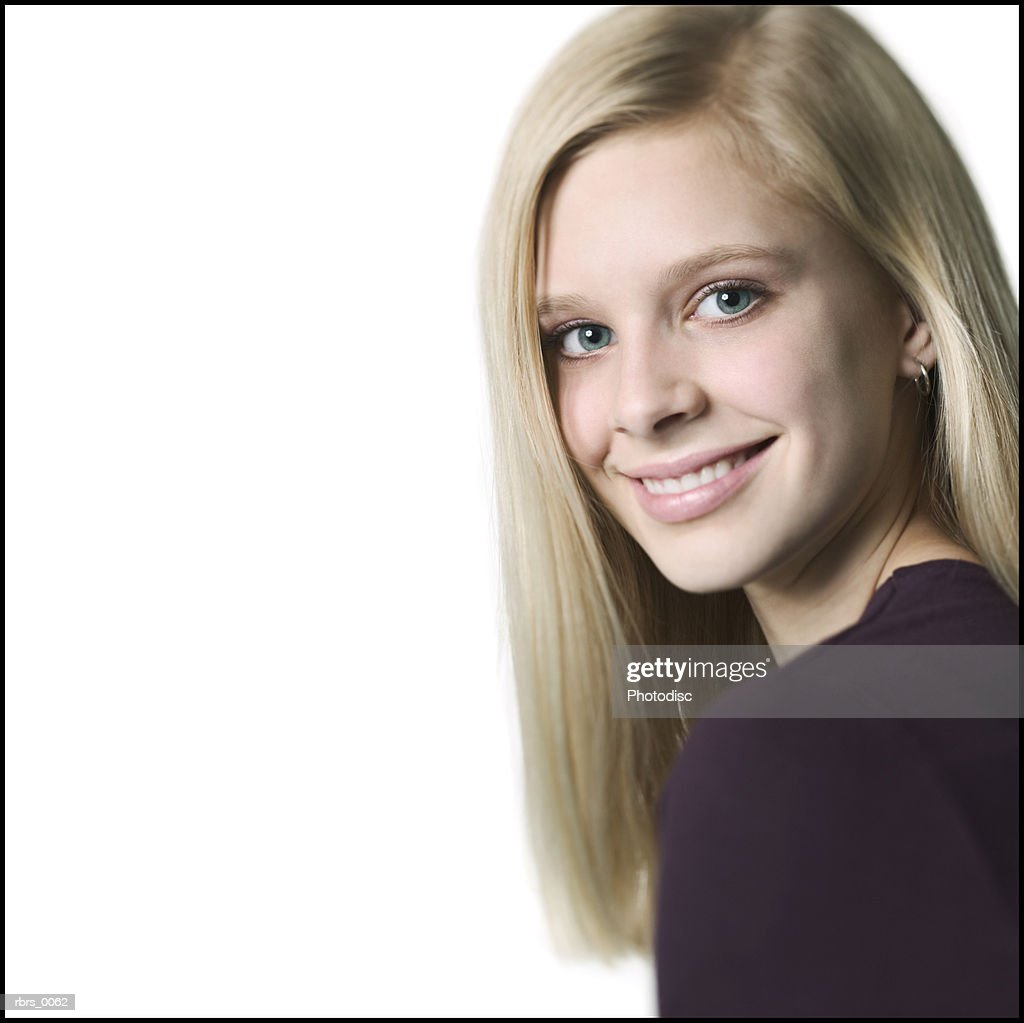 medium close up shot of a teenage female in a purple shirt as she looks over her shoulder and smiles : Foto de stock