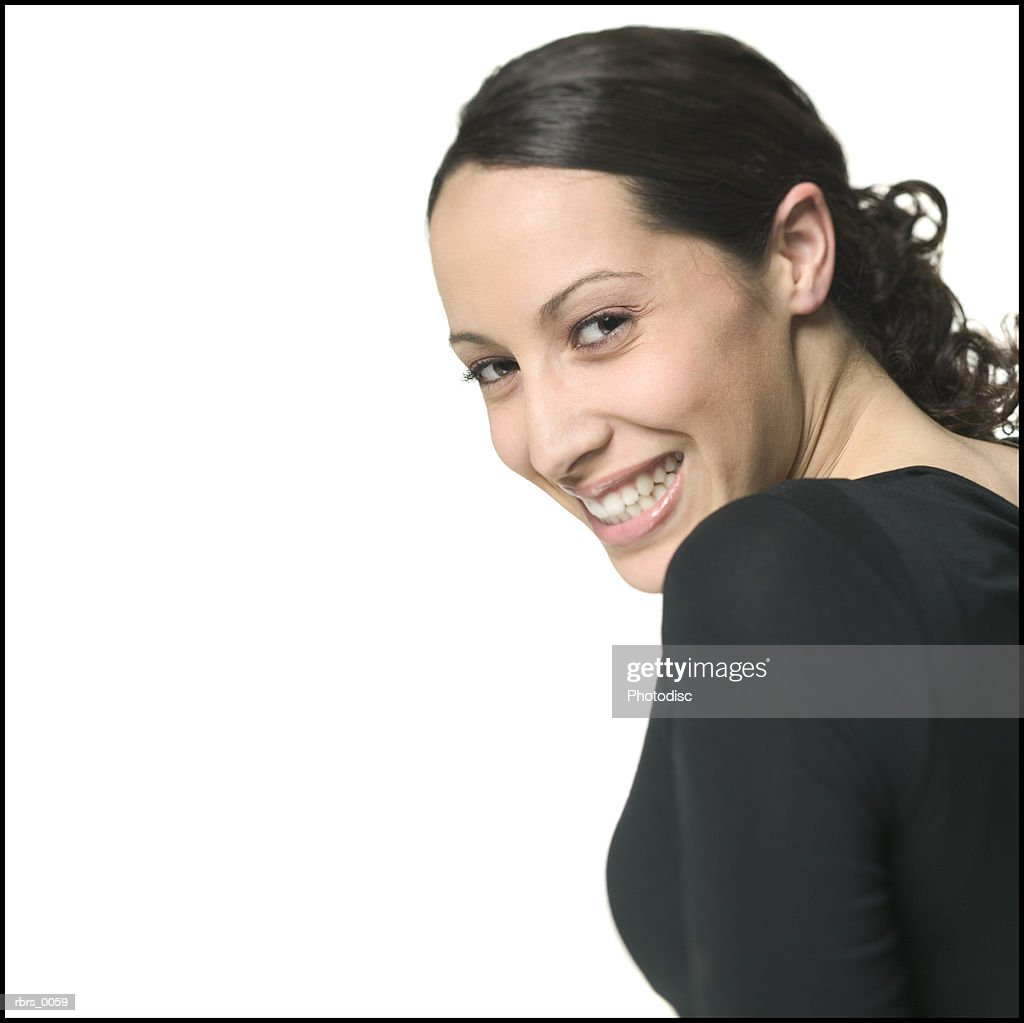 medium close up shot of a young adult woman as she glances over her shoulder and smiles : Stockfoto
