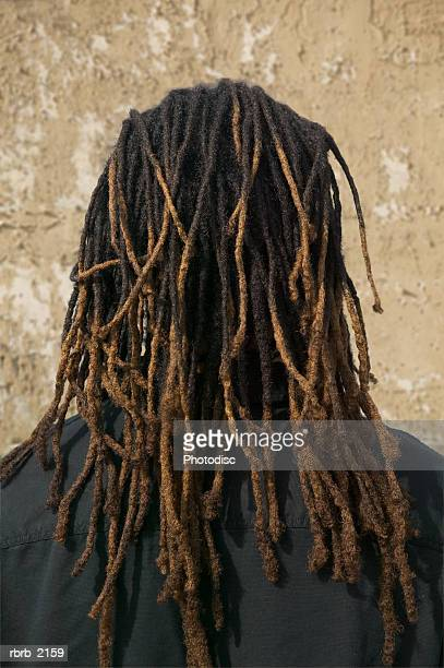 medium close up shot of the back of the head of a young adult male with dreadlocks