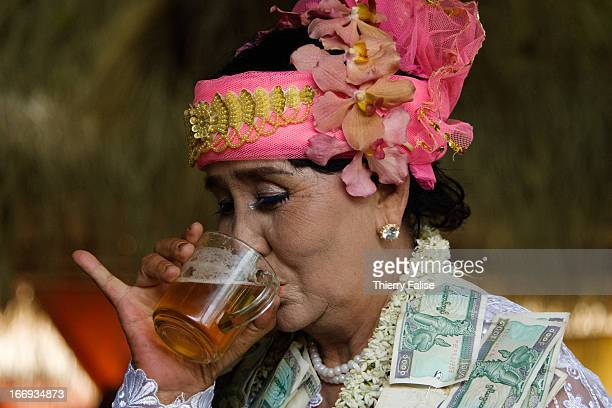 Medium drinks beer during a dance at the Taungbyon festival. Every year in August, hundreds of thousands of people from all over Myanmar gather for a...