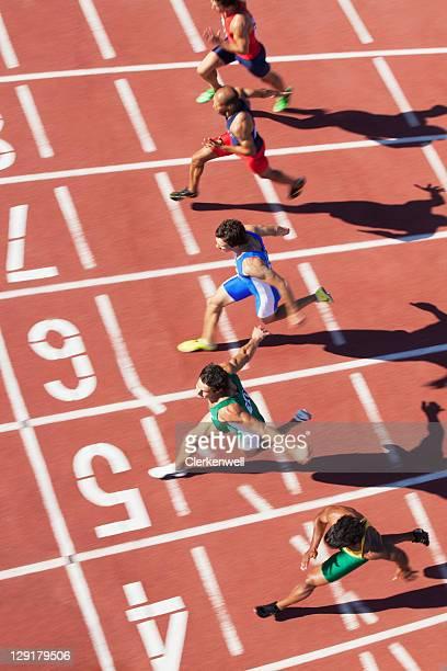 Medium group of male athletes running on running track
