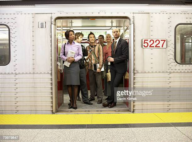 medium group of people standing in subway train doorway - subway station stock pictures, royalty-free photos & images
