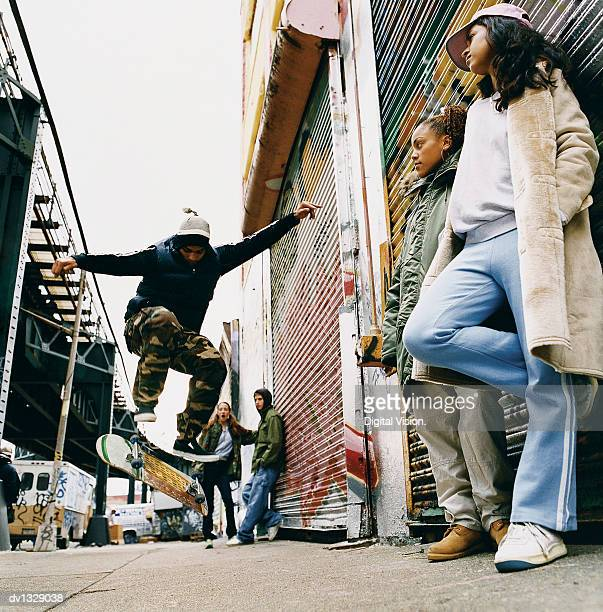 medium group of teenagers in a back alley watching stunts on a skateboard - black alley stock photos and pictures