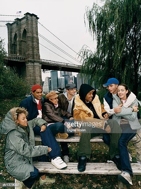 medium group of teenagers sitting on a bench in a park - medium group of people photos et images de collection