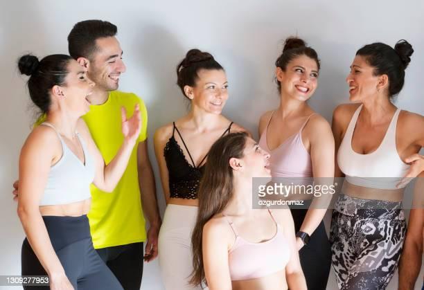 groupe moyen d'étudiants de yoga bavardant et riant ensemble dans le cours de yoga - medium group of people photos et images de collection
