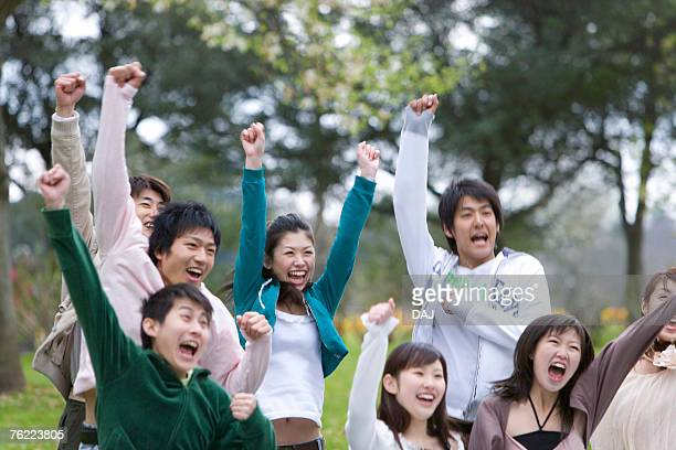 medium group of young people holding fists up in the air, cheering, front view, japan - cheering ストックフォトと画像