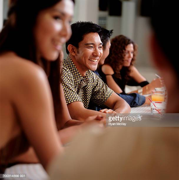 Medium group of young people sitting at bar in club