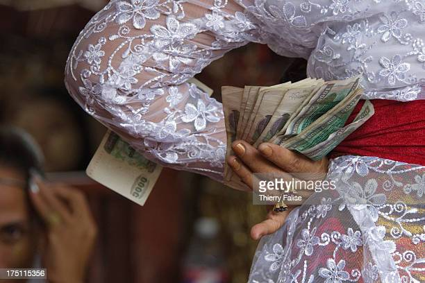 Medium holds money offered by revellers during a dance at the Taungbyon nat festival. Every year in August, hundreds of thousands of people from all...