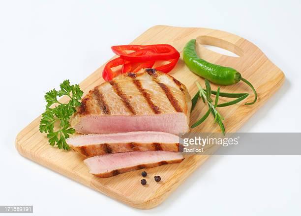 medium pork steak with spices on a cutting board