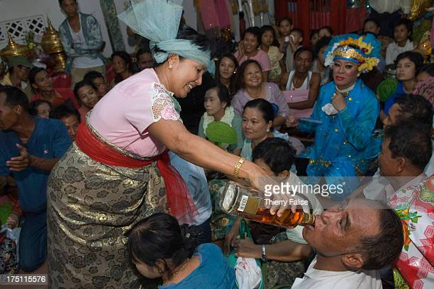 A medium pours whisky into the mouth of a reveller attending a dance in a shrine during the Taungbyon nat festival Every year in August hundreds of...