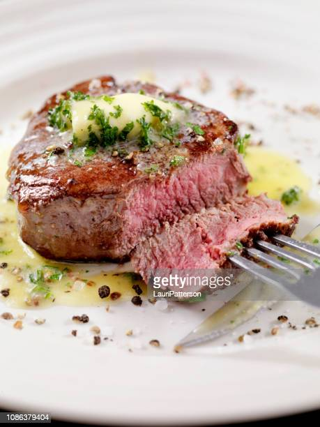 medium rare fillet mignon steak with herb garlic butter - juicy stock photos and pictures