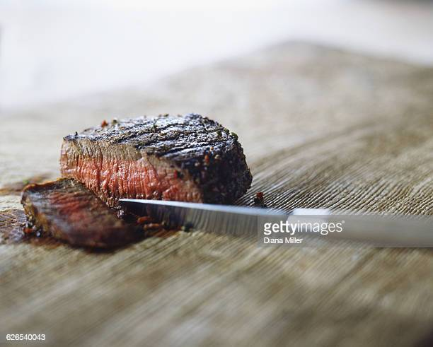 Medium rare steak with peppercorns, sliced with knife