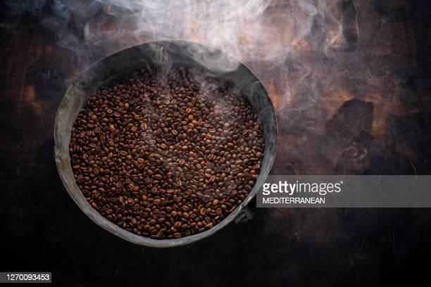 ミディアムローストコーヒー豆は、木材の焙煎パンでスモーキー - ロースト ストックフォトと画像